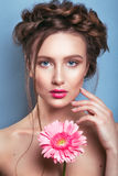 Portrait of romantic young woman with pink flower looking at camera on blue background. Spring fashion photo. Inspiration of spri Royalty Free Stock Photo