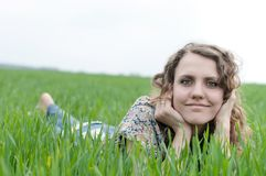 Portrait of romantic, young woman with short hair lying on green grass, dreams Stock Photos