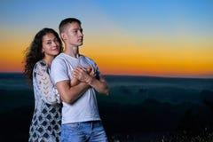 Portrait romantique de couples au coucher du soleil sur le paysage extérieur et beau et le ciel jaune lumineux, concept de tendre Photos stock