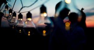 Portrait romantique des couples affectueux étreignants derrière la ficelle des lumières pendant le coucher du soleil longueur 4k clips vidéos