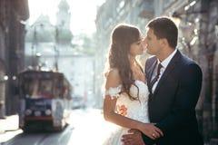 Portrait romantique en gros plan des nouveaux mariés attirants étreignant au fond de la vieille ville pendant le coucher du solei Photo libre de droits