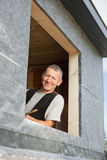 Portrait of a roofer looking by a dormer window Stock Photos
