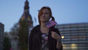Portrait roux de femme tenant le drapeau américain des Etats-Unis avec le bâtiment en verre à l'arrière-plan - voyageur et explor banque de vidéos