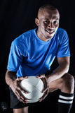 Portrait of rugby player with ball smiling while kneeling Royalty Free Stock Photos