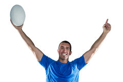 Portrait of rugby player in blue jersey holding ball with arms raised Royalty Free Stock Image