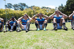 Portrait of rugby players exercising at grassy field Royalty Free Stock Photography