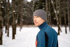 Portrait of a runner from the back, dressed in warm sportswear and preparing to run. In the winter forest royalty free stock photography