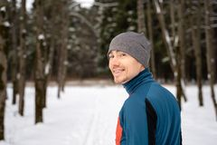 Portrait of a runner from the back, dressed in warm sportswear and preparing to run. In the winter forest stock image