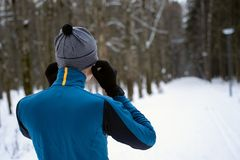 Portrait of a runner from the back wearing headphones and preparing to run in the winter forest. Portrait of a runner from the back, dressed in warm sportswear royalty free stock images