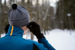 Portrait of a runner from the back wearing headphones and preparing to run in the winter forest. Portrait of a runner from the back, dressed in warm sportswear royalty free stock photos