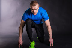 Portrait of runner on start, ready to go. on a dark background Stock Image