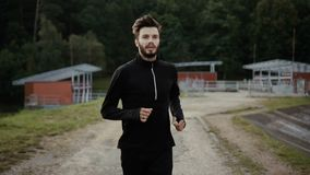 Portrait of running bearded Caucasian sportsman. Close up slow motion handsome male. Calm outdoors fitness meditation. stock footage