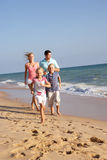 Portrait Of Running Family On Beach. Holiday Stock Image