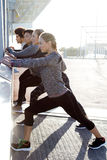 Portrait of running people doing stretching in the city. Royalty Free Stock Photos