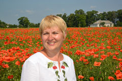 Portrait of the rural woman against a poppy field Royalty Free Stock Images