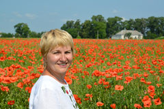 Portrait of the rural woman against a poppy field Royalty Free Stock Photos