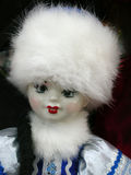 Portrait of a Russian doll at the flea markets. Vertical shot of traditional dark eyed Russian doll with white fur hat, souvenir from Saint Petersburg markets Stock Images