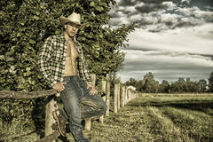 Portrait of rustic man in hat with unbuttoned shirt leaning on wooden fence Royalty Free Stock Photos