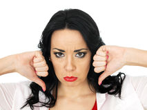 Portrait of a Sad Angry Negative Young Hispanic Woman with Thumbs Down. Portrait of a Sad Angry negative sulky Young Hispanic Woman with long black curly hair royalty free stock photo