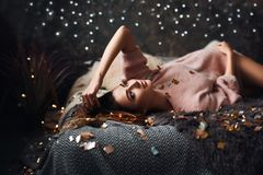 Portrait of sad attractive young woman with tinsel confetti and garland lights celebrating alonein dark room. New year`s stock photos