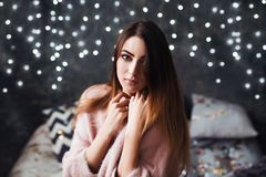 Portrait of sad attractive young woman with tinsel confetti and garland lights celebrating alonein dark room. New year`s stock photo