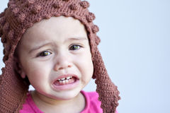 Portrait of sad baby girl - 11 months old. A pretty 11-month-old baby has a sad and crying expression on her face.  She wears a pink top and brown knitted hat Royalty Free Stock Photography