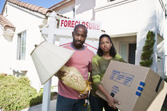Portrait Of Sad Bankrupt Couple Moving Out Of House. Portrait of sad bankrupt couple with lamp and cardboard box while moving out of house royalty free stock photo