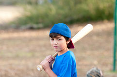 Portrait of sad baseball boy with wooden bat. Outdoor portrait of a young baseball kid in blue shirt looking sad and depressed holding a wooden bat Stock Image