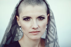 Portrait of sad beautiful Caucasian white young bald girl woman with shaved hair head, scarf cover, looking in camera Stock Images