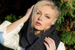 Portrait of a sad beautiful girl blonde in a headscarf in a public Park on a Sunny autumn day Royalty Free Stock Photos