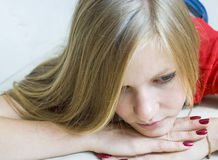 Portrait of sad beautiful young girl. Lying on her hands Royalty Free Stock Images