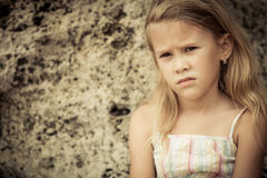 Portrait of sad blond little girl sitting on the beach Stock Photos