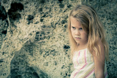Portrait of sad blond little girl sitting on the beach Stock Photo