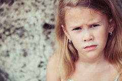 Portrait of sad blond little girl sitting on the beach Stock Images