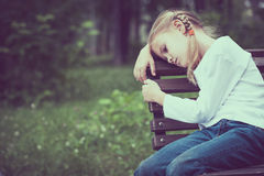 Portrait of sad blond little girl sitting on bench Royalty Free Stock Photography