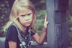 Portrait of sad blond little girl sitting on the bridge Royalty Free Stock Image