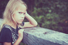 Portrait of sad blond little girl sitting on the bridge Royalty Free Stock Photos