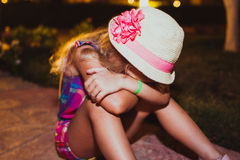 Portrait of sad blond little girl sitting on the ground. Royalty Free Stock Photos