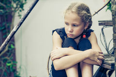 Portrait of sad blond teen girl. Sitting on the stairs at the day time Stock Photos