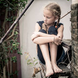 Portrait of sad blond teen girl. Sitting on the stairs at the day time Royalty Free Stock Photography