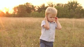 Portrait of sad boy on a background of a dry field. Portrait of a sad boy of four years against the background of a dry summer field at sunset stock video footage
