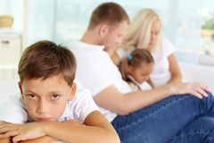 Sadness. Portrait of sad boy on background of his parents and sister Royalty Free Stock Images