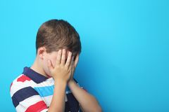 Sad boy. Portrait of sad boy on blue background stock images