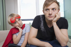 Portrait of sad boy dressed in superhero costume sitting with father on sofa bed at home Royalty Free Stock Image
