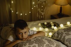 Portrait of Sad  boy lying in bed evening in dark against the ba Stock Images