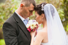 Portrait of sad bride and groom looking at bouquet Stock Photo