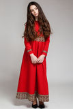 Portrait of a sad brunette girl with long hair in a red dress. Full-length,  gray background Royalty Free Stock Photo