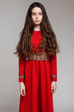 Portrait of a sad brunette girl with long hair in a red dress. Gray background Royalty Free Stock Images