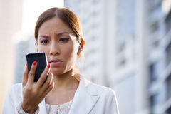 Portrait sad business woman typing sms phone street Stock Image