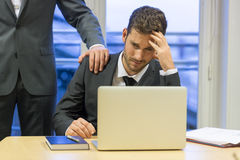 Portrait of sad businessman with her boss at background. Hand on Royalty Free Stock Photos